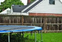 Dangerous live downed power line draped across fence and trampoline
