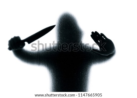 Stock Photo Dangerous man behind frosted glass with a knife in his hand. Halloween. Black and white image