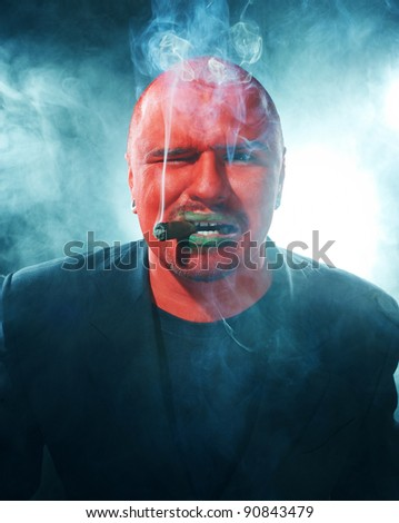 Dangerous man with red face smoking cigar on scary background.