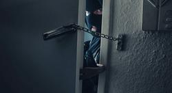 dangerous masked burglar with crowbar breaking into a victim's home door