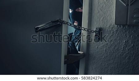 dangerous masked burglar with crowbar breaking into a victim's home door Stockfoto ©