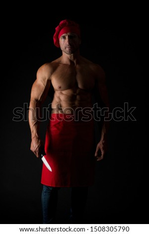 Dangerous occupation. Professional cook on black background. Man cook with muscular torso wearing chefs hat and apron. Chief cook with six pack abs holding kitchen knife. Chopping with sharp blade.