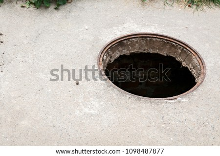 Dangerous opened manhole hole cover, danger for people who walking on the street in the city