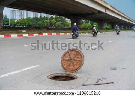 Dangerous opened manhole hole cover, opened sewerage hatch with traffic on background