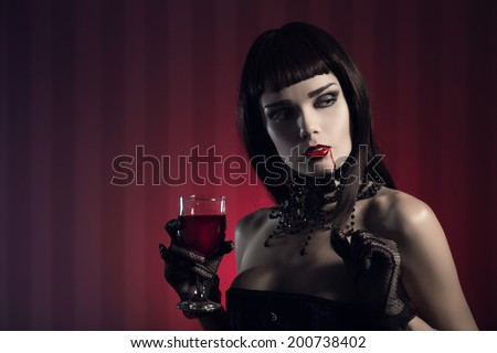 Dangerous sexy vampire girl in glamorous outfit with glass of wine or blood