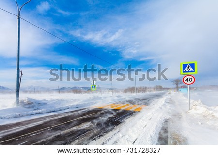 Dangerous snowing road with crosswalk, bus stop and road signs for driving cars and public transport during  blizzard or  snowstorm. #731728327