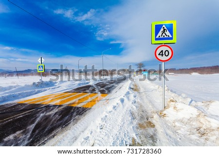 Dangerous snowing road with crosswalk, bus stop and road signs for driving cars and public transport during  blizzard or  snowstorm. #731728360