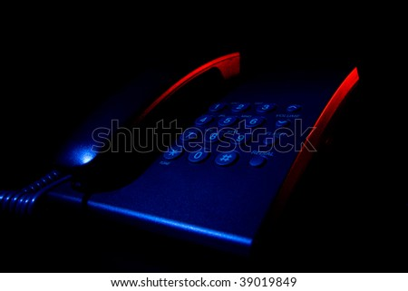 Dangerous talk - phone silhouette in the dark, blue and red light