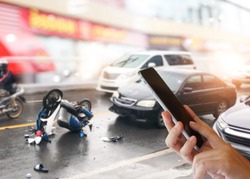 Dangerous traffic on the road, Careless driving car collides with motorcycle. Woman hands using smartphone calling ambulance and car insurance service. Concept  car accidents, emergency and insurance.