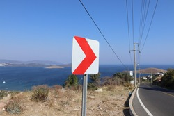 Dangerous turn right, red and white roadsign on road side