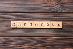 dangerous word written on wood block. dangerous text on cement table for your desing, concept.