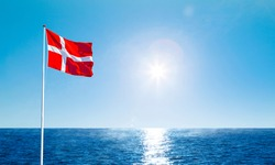 Danish flag in the wind against a blue sky