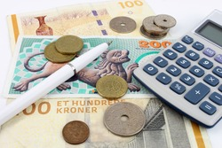 Danish Kroner notes and coins arranged with a calculator and pen to symbolize finance.