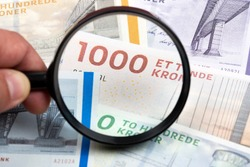 Danish money in a magnifying glass a business background