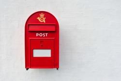 Danish red mailbox on white wall background