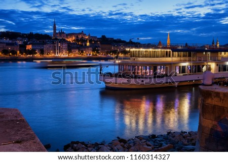 Danube River at blue hour twilight in city of Budapest, Hungary, cruise and dinner boat, view from Pest to Buda side.