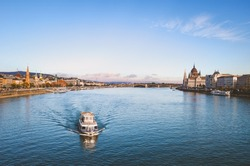 Danube river in Budapest, Hungary with floating sightseeing boat on the water. Historical center on both sides of the river. Hungarian Parliament building in the background. Budapest cityscape.