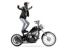 Daredevil riding a customized motorbike and standing on the seat isolated on white background