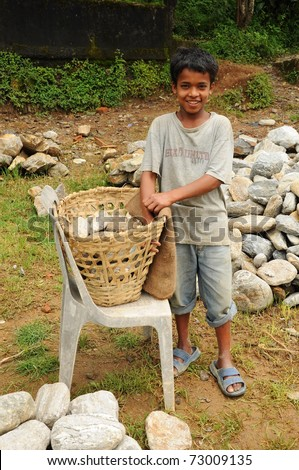 DARJEELING, INDIA - AUGUST 16: Unidentified young boy works hard as porter instead going to school on August 16, 2010. Child's work is a global problem. INDIA