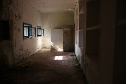 Dark abandoned room in disrepair, falling into decay, illuminated by a sun ray through two small very tiny windows