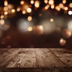 Dark abstract background with christmas lights in front of a  table
