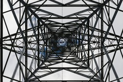 Dark abstract image of the inside of an electrical pylon. Interior skyward view, looking up, lattice structure creates an industrial themed pattern.