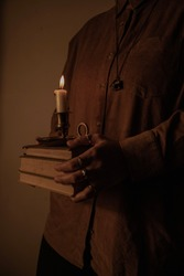 Dark academia composition with antique books and candle
