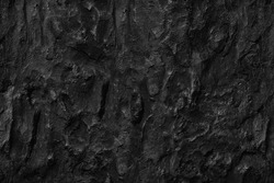 Dark aged shabby cliff face volcanic hillside. Coarse, rough gray volcanic stone or rock texture of mountains, background and copy space for text on theme geology and volcanic eruption study.