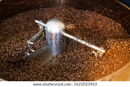 Dark and aromatic coffee beans in a modern roasting machine.Selective Focus