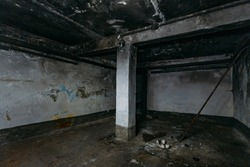 Dark and creepy dirty abandoned underground basement afrer fire. Walls in black soot