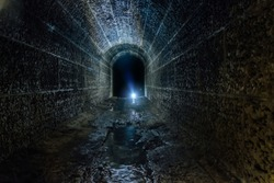 Dark and creepy old historical vaulted flooded underground drainage tunnel.