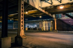 Dark and eerie Chicago urban city street night scenery with elevated CTA train tracks, vintage industrial warehouses and factories.