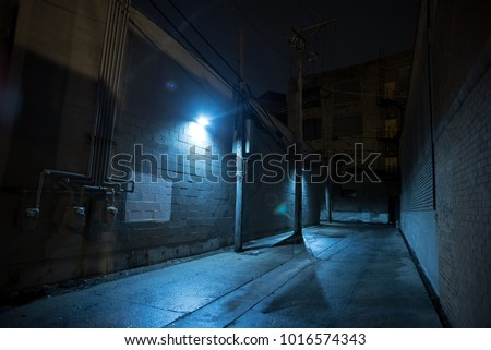 Dark and eerie urban city alley at night. #1016574343