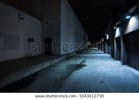 Dark and eerie urban city alley at night #1043612758