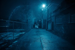 Dark and eerie urban city alley at night in the winter