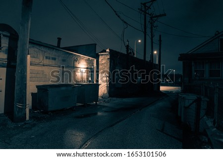 Dark and eerie urban city alley at nightin the winter
