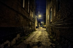 Dark and eerie urban city cobblestone brick paved alley at night