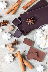 Dark and milk chocolate, cinnamon, anise star, brown sugar, marshmallow, meringue and milk over light background. Ingredients for making hot chocolate. Top view.