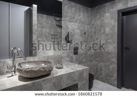 Dark and modern bathroom with gray wall tiles, stone like washbasin and big mirror Foto stock ©