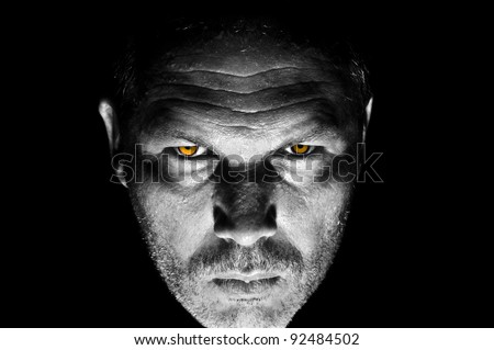 Dark and moody portrait of serious looking male adult with bright orange intimidating eyes