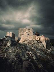 Dark and moody view of Hrusov Castle in Europe (Slovakia) before the storm. Old Ruins of castle on the dark rocks with rainbow on background.  Dramatic shot of castle on the hill with misty sky.