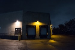 Dark and scary city warehouse loading dock and entrance door at night.