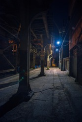 Dark and scary downtown urban city street alley under an eerie and illuminated vintage industrial railroad subway bridge at night