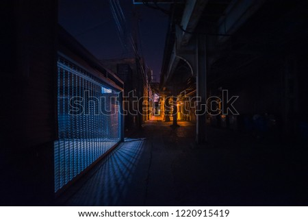 Dark and scary downtown urban city street alley under an eerie vintage industrial railroad subway bridge with an illuminated gate fence at night