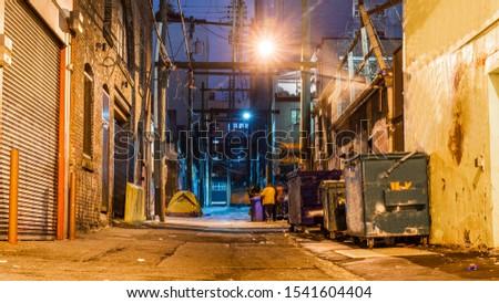 Dark and scary vintage cobblestone brick city alley at night in Vancouver, British Columbia, Canada. Stockfoto ©