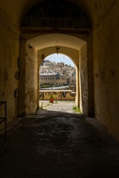 Dark arched tunnel with bright exit at the end in Malta Senglea