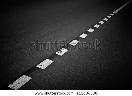 Dark asphalt road background with marking lines. Close up photo