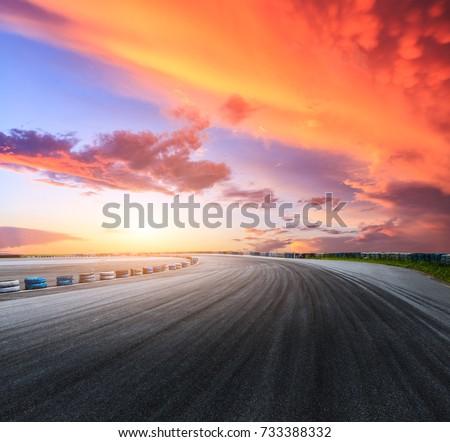 Dark asphalt road circuit and beautiful sky at sunset #733388332