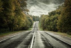 Dark asphalt road under a storm sky.