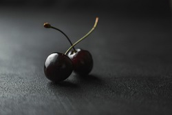 Dark atmospheric image of two ripe red cherries on a joined stalk on a black reflective surface against a dark background with copyspace.